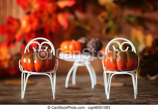 fresh pumpkin in interior wooden room on chair - csp46051083