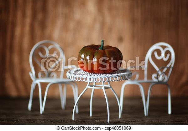 fresh pumpkin in interior wooden room on chair - csp46051069
