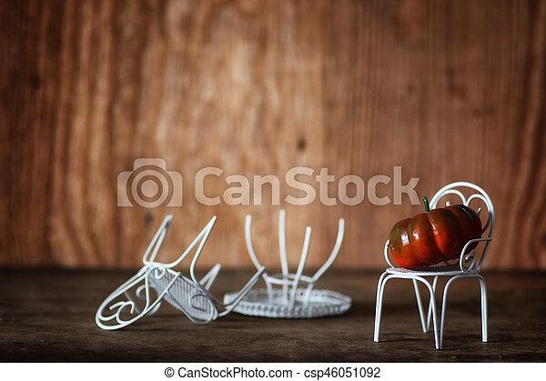 fresh pumpkin in interior wooden room on chair - csp46051092