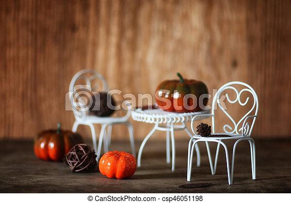 fresh pumpkin in interior wooden room on chair - csp46051198