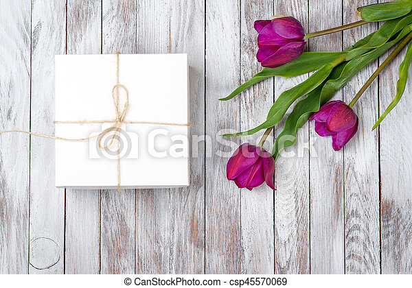 Fresh purple tulips bouquet and gift box on wooden background. Space for text. Top view. - csp45570069