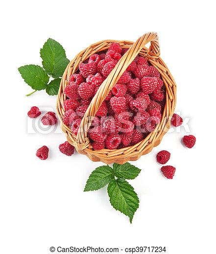 Fresh raspberries in wicker basket with green leaves - csp39717234