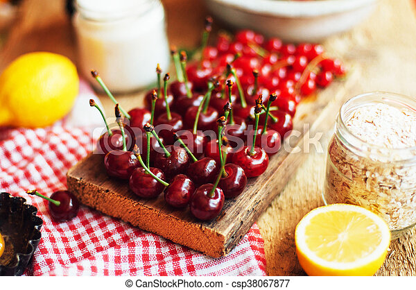 Fresh red cherries on a rustic wooden table. Ripe cherries i o - csp38067877