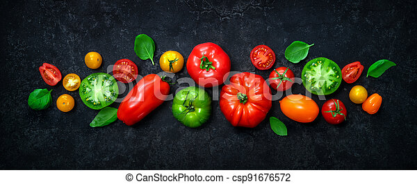 Fresh ripe tomatoes of different varieties with basil leaves on dark panoramic stone background - csp91676572