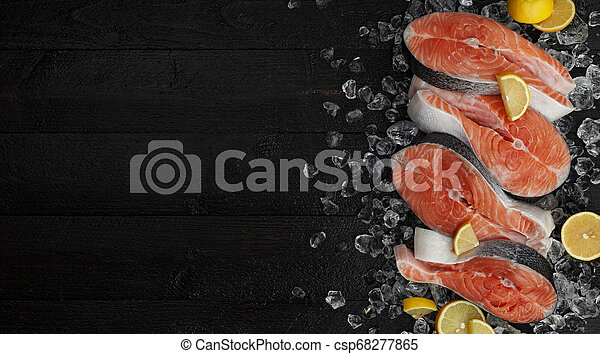 Fresh salmon steaks on black background, piece of chilled red fish on ice, top view - csp68277865