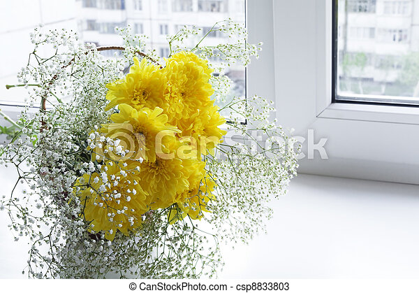 Fresh spring flowers in a vase on a window sill - csp8833803