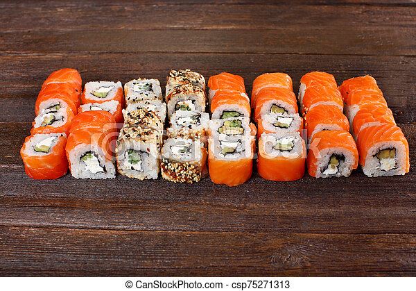 Fresh sushi roles on a wooden plate - csp75271313