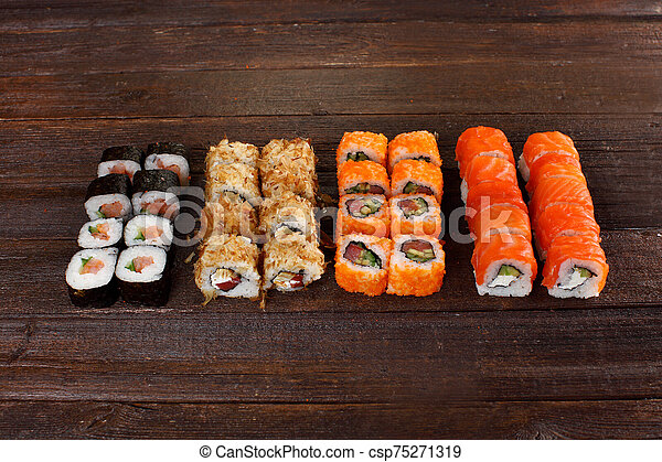 Fresh sushi roles on a wooden plate - csp75271319