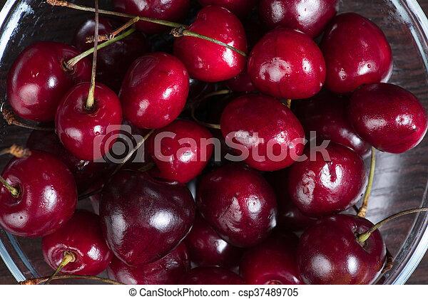 Fresh sweet cherries in bowl on dark background, top view