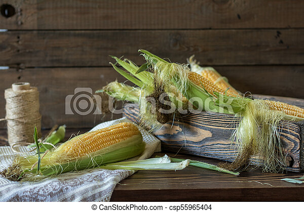 Fresh sweet corn on cobs on rustic wooden table - csp55965404
