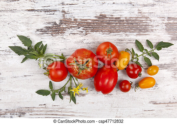 Fresh tomato fruits on wooden background from above. - csp47712832