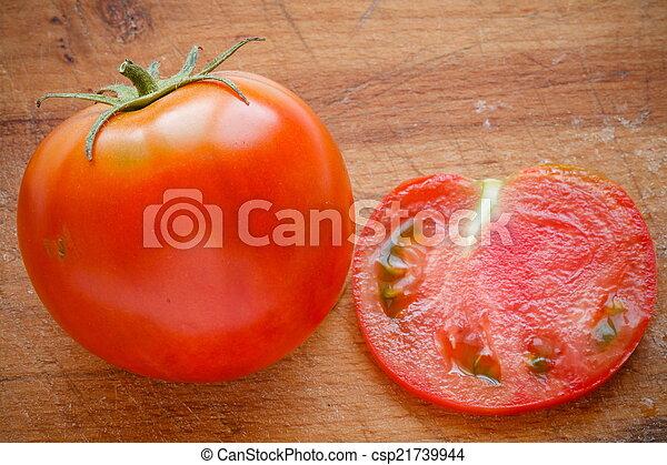 fresh tomato on wooden cutting board - csp21739944