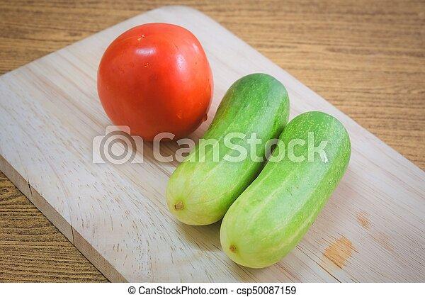 Fresh Tomato with Cucumbers on Cutting Board - csp50087159