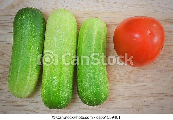Fresh Tomato with Cucumbers on Cutting Board - csp51559401