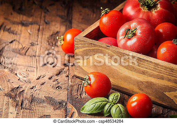 fresh tomatoes in a wooden crate - csp48534284
