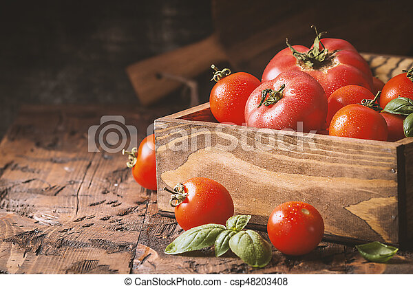 fresh tomatoes in a wooden crate - csp48203408
