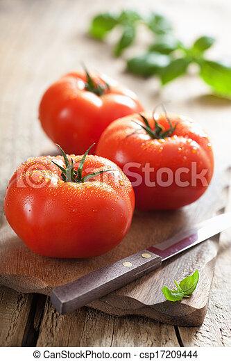 fresh tomatoes on cutting board - csp17209444