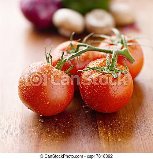 fresh tomatoes on cutting board - csp17818392
