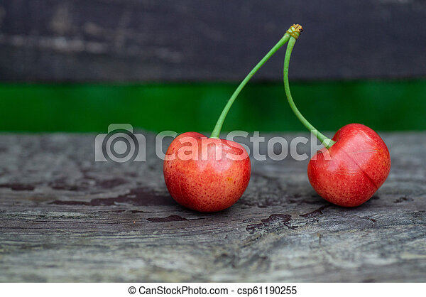 Fresh two sweet cherries on a wooden bench background. fresh ripe cherries. 2 cherries in the open air on the background - csp61190255