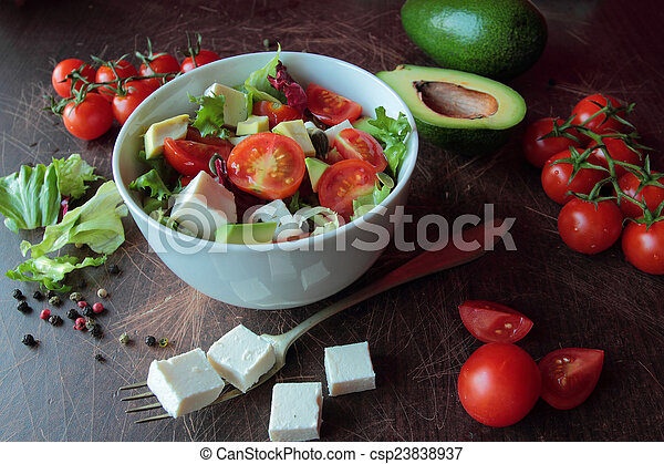 Fresh vegetable salad on a wooden table - csp23838937