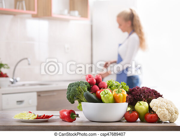 Fresh vegetables on table with woman in background - csp47689407