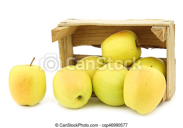 fresh yellow apples and a cut one in a wooden crate - csp46990577