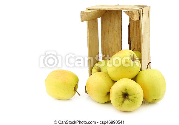 fresh yellow apples and a cut one in a wooden crate - csp46990541