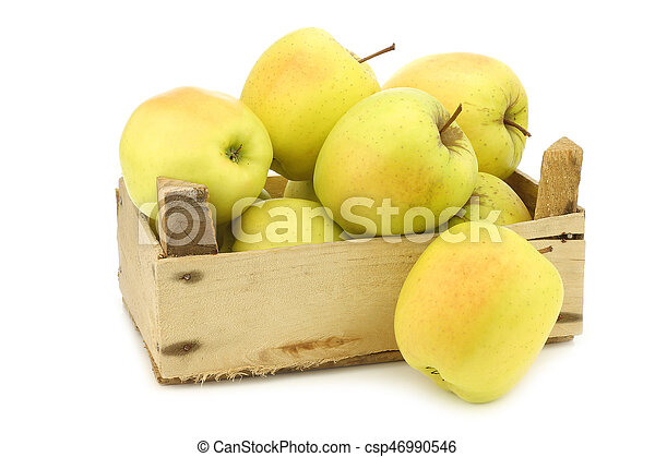 fresh yellow apples and a cut one in a wooden crate - csp46990546