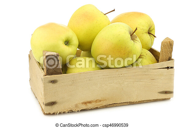 fresh yellow apples and a cut one in a wooden crate - csp46990539