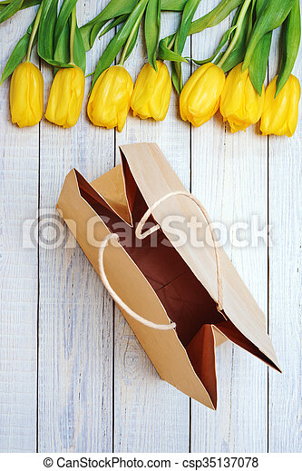 Fresh yellow tulips with empty paper bag on wooden background. - csp35137078