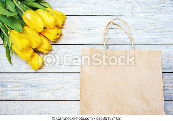 Fresh yellow tulips with empty paper bag on wooden background. - csp35137102