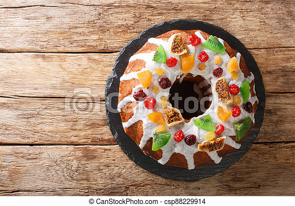 Freshly baked cake with raisins, dried apricots, dried cherries, kiwi and cranberries and icing close-up on a board. horizontal top view - csp88229914