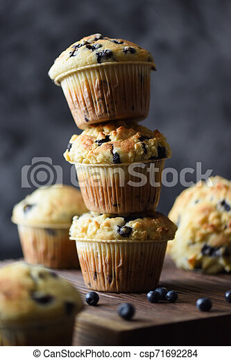 Freshly baked crumble muffins with wild bilberries arranged in unstable pile on dark background copy space. Low key still life with natural lighting - csp71692284