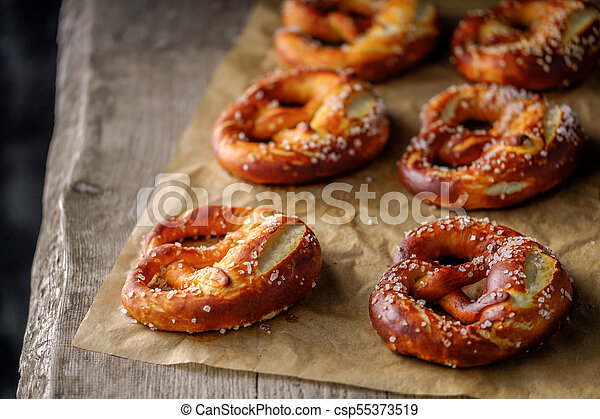 Freshly baked home soft pretzel with salt on craft paper for baking. - csp55373519