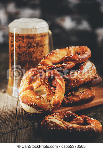 Freshly baked homemade soft pretzel with salt on rustic wooden table with glass of beer - csp55373565