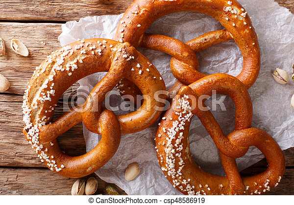 Freshly baked soft pretzel with generous sprinkling of coarse salt close-up. horizontal top view - csp48586919