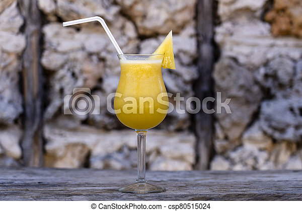 Freshly squeezed juice from pineapple in a glass goblet on the background of an old stone wall - csp80515024