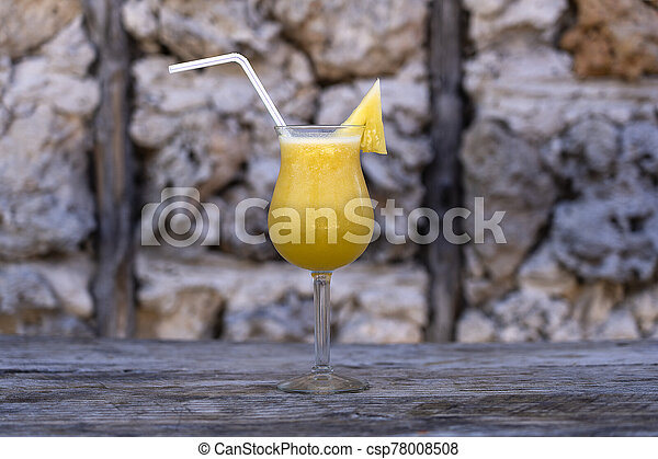 Freshly squeezed juice from pineapple in a glass goblet on the background of an old stone wall - csp78008508