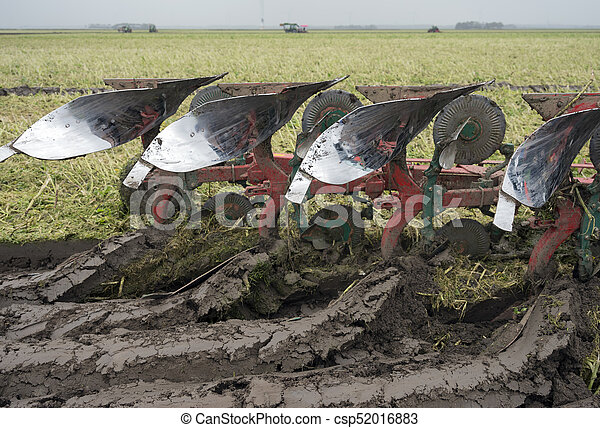 fresly plowed land and tractor with plough - csp52016883
