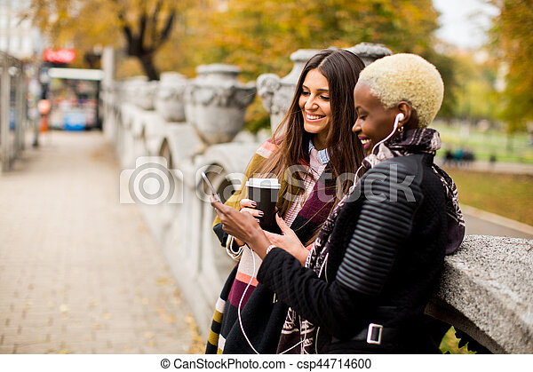 frican american and caucasian woman posing outside - csp44714600