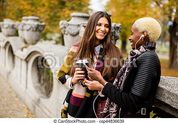 frican american and caucasian woman posing outside - csp44836639