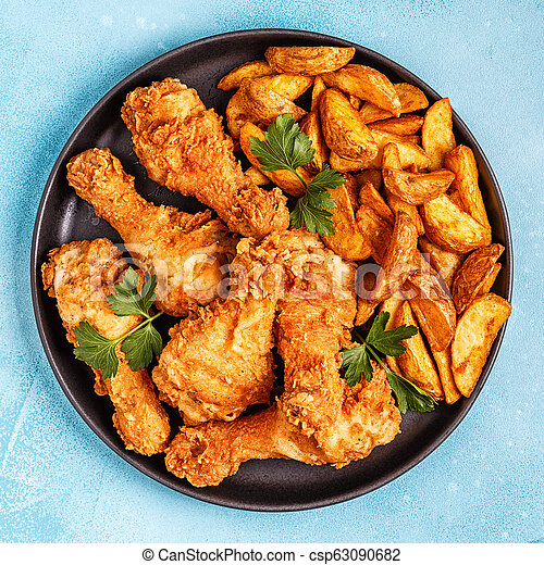 Fried chicken legs with potatoes. - csp63090682
