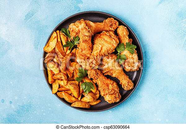 Fried chicken legs with potatoes. - csp63090664
