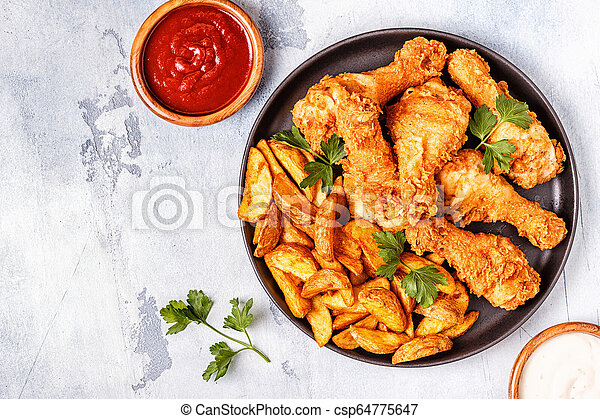 Fried chicken legs with potatoes. - csp64775647