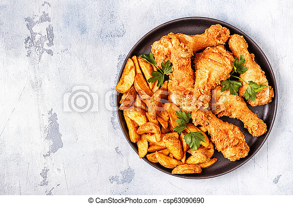 Fried chicken legs with potatoes. - csp63090690