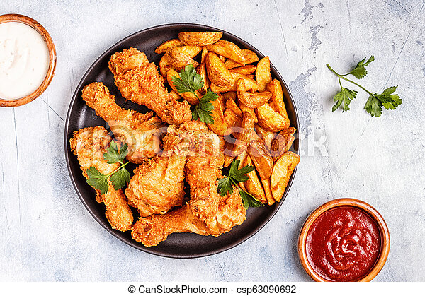 Fried chicken legs with potatoes. - csp63090692
