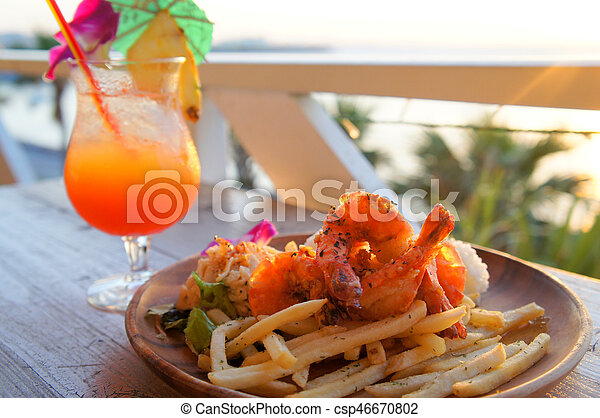 Fried chips with shrimps and juicy fruit in resort - csp46670802