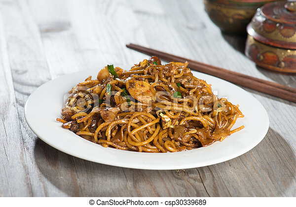 Fried Penang Char Kuey Teow which is a popular noodle dish in Malaysia, Indonesia, Brunei and Singapore - csp30339689