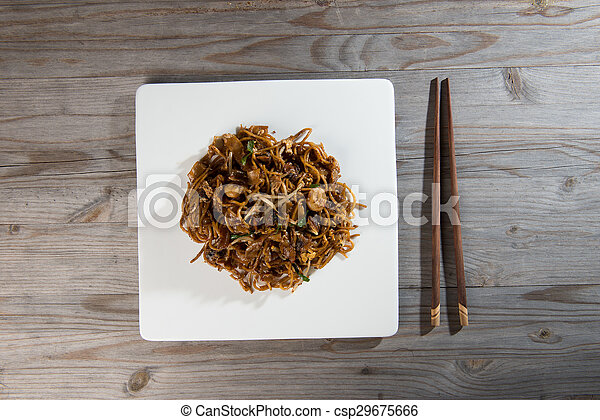 Fried Penang Char Kuey Teow which is a popular noodle dish in Malaysia, Indonesia, Brunei and Singapore - csp29675666