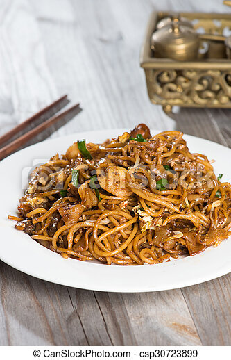 Fried Penang Char Kuey Teow which is a popular noodle dish in Malaysia, Indonesia, Brunei and Singapore - csp30723899